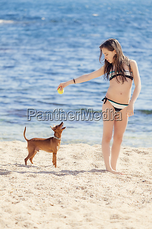 girl playing with dog on the