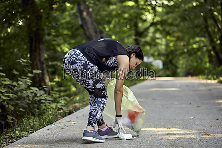 young woman plogging on forest path