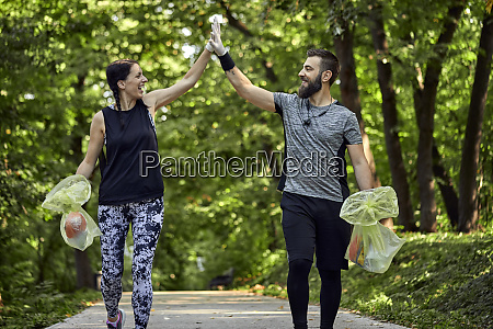 happy couple plogging on forest path