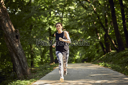 sporty young woman running on forest