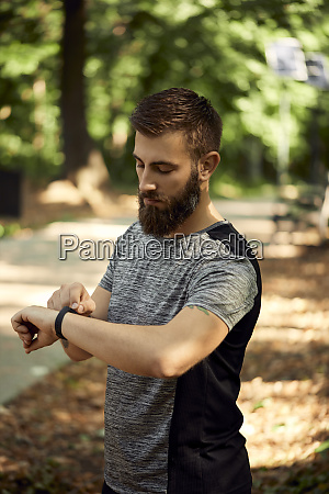 sporty man in forest checking his