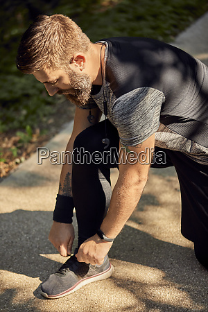 sporty man tying his shoe before