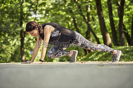sporty young woman exercising on forest