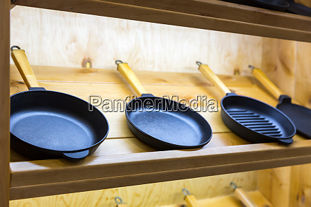 frying pans on wooden shelf closeup