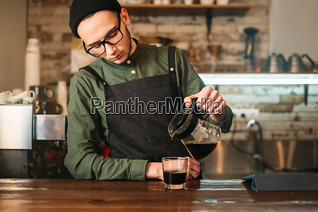 barman pours coffee in a glass