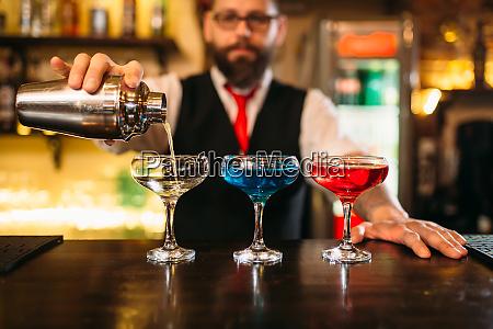 bartender making alcohol beverages in nightclub