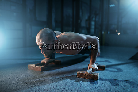 sportsman makes pushups exercises on training