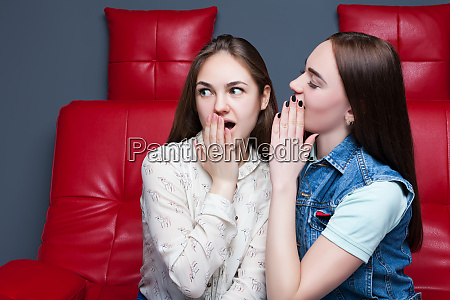 two pretty girls gossiping on red
