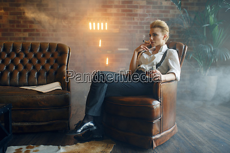 woman sitting in chair with whiskey