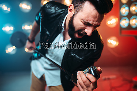 bearded performer with microphone sing a