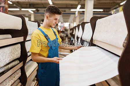 male builder choosing wallpapers in hardware