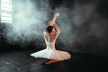 female classical ballet performer sitting on
