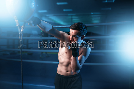 boxer in bandages training with bag