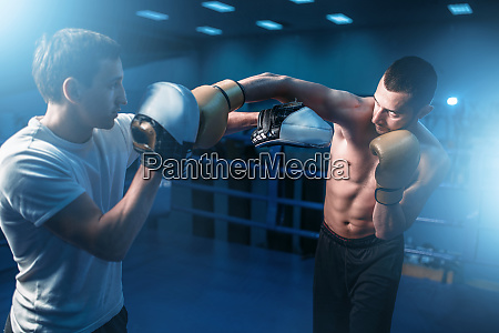 boxer in gloves exercises with personal