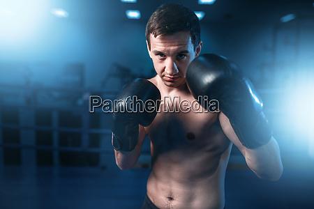 portrait of muscular boxer in black