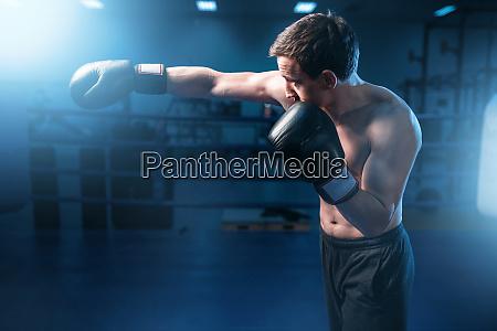 muscular boxer in black gloves training