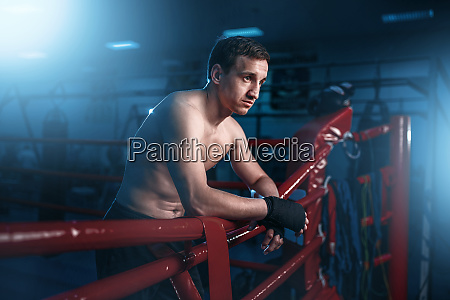 boxer in black handwraps poses on