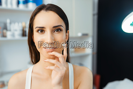 patient shows cream on finger cosmetician
