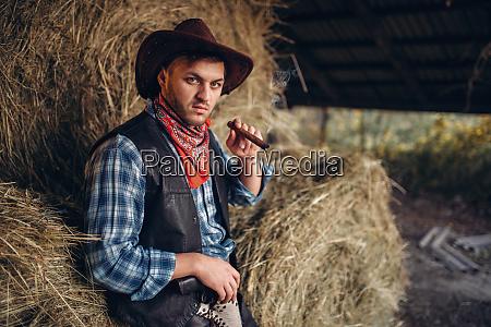 brutal cowboy smokes cigar haystack on