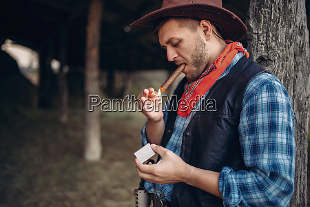 brutal, cowboy, lights, a, cigar, with - 28061827
