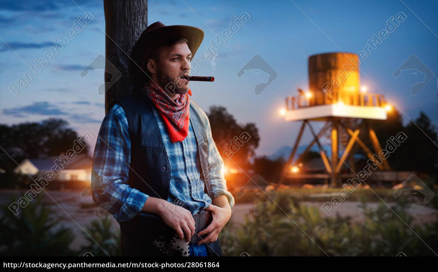 brutal, cowboy, smokes, a, cigar, on - 28061864