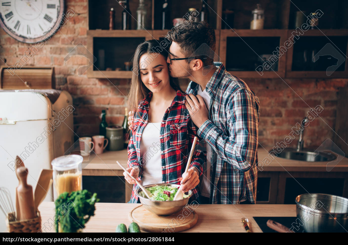husband, kissing, wife, on, kitchen, while - 28061844