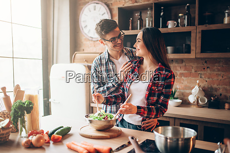 husband, kissing, wife, on, kitchen, while - 28061907