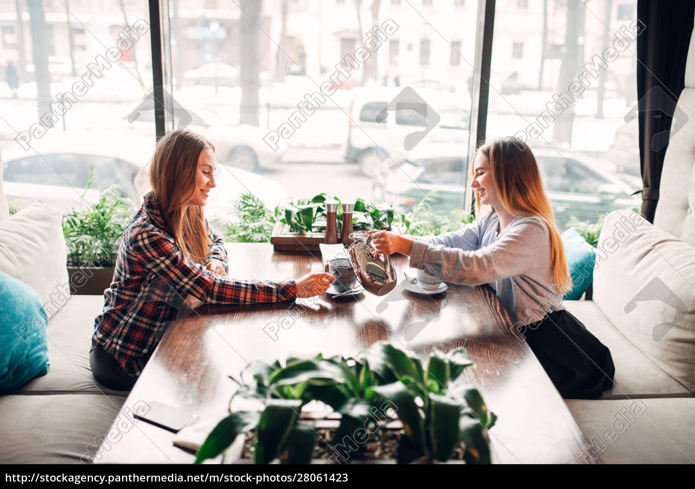 two, girlfriends, met, in, a, cafe - 28061423