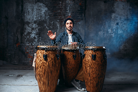 drummer playing on wooden bongo drums