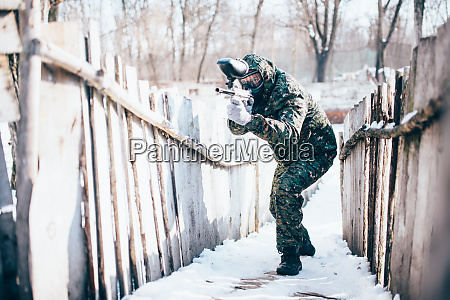 paintball player with marker gun in