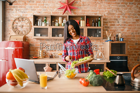 black woman looking recipe on laptop