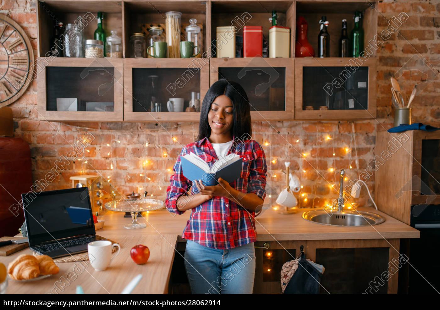 black, woman, looking, recipe, book, on - 28062914