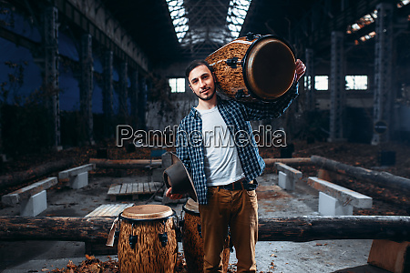 drummer, holds, wooden, drum, on, the - 28062702
