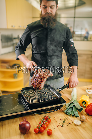 male, person, cooking, meat, in, a - 28062210