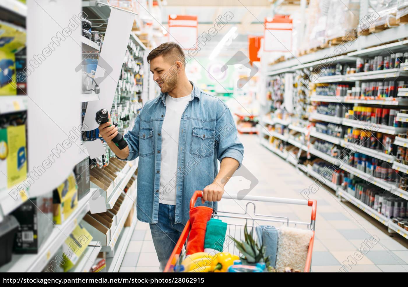 man, choosing, electric, screwdriver, in, supermarket - 28062915