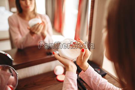 woman, applies, hand, cream, to, skin - 28062102