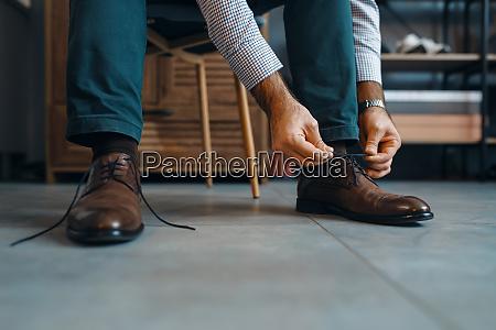 man tries on repaired shoes footwear