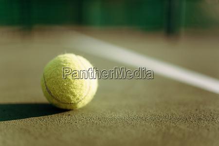 tennis ball on ground coverage closeup