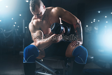 muscular male athlete lifting dumbbells