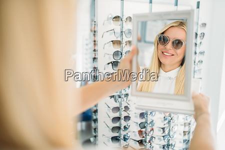 female, customer, shooses, sunglasses, in, optics - 28063398