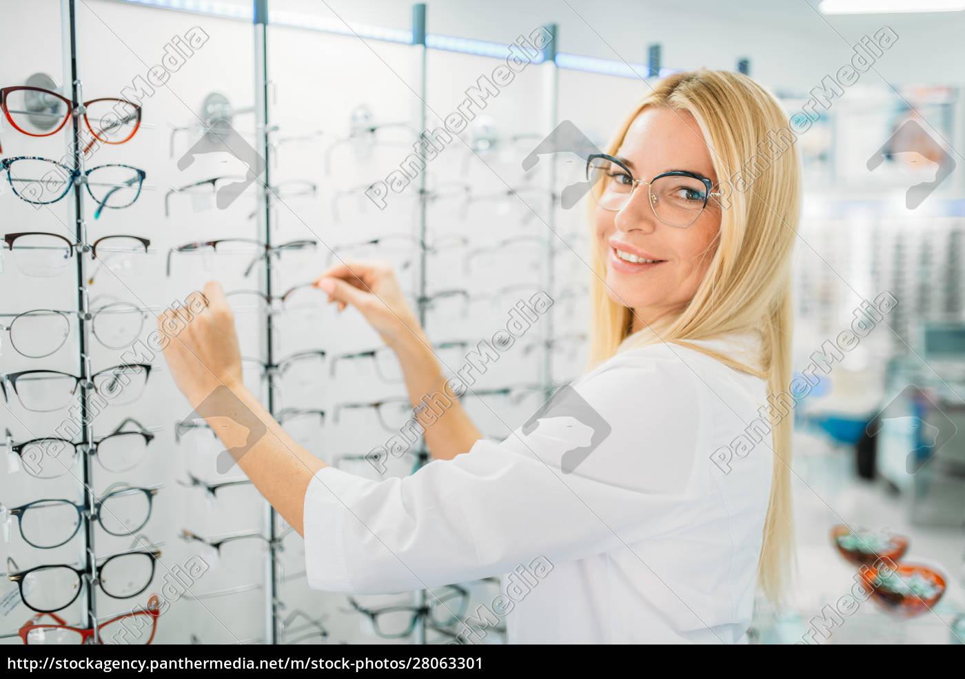 female, optometrist, shows, glasses, in, optics - 28063301