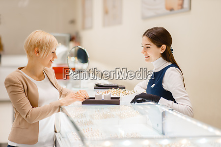woman, choosing, wedding, rings, in, jewelry - 28063005