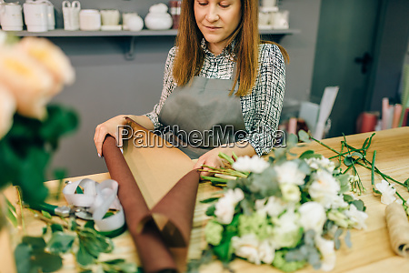 florist hands cuts flower composition with