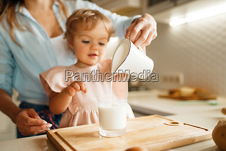 young mother and kid pours milk