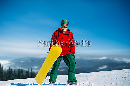 snowboarder in glasses poses with board