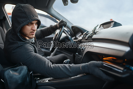 car robber searches the glove compartment