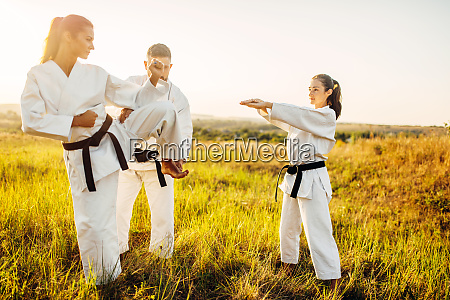 master teaches karate fighters the correct