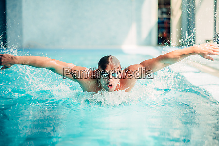 athletic swimmer swims in butterfly style