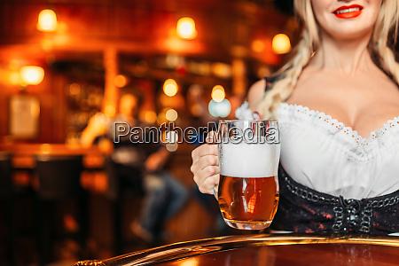 large breasted waitress holds mug