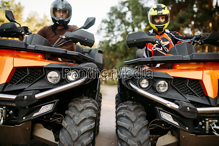 two riders on quad bikes front